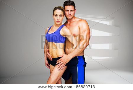 Bodybuilding couple against digitally generated room with bordered up window