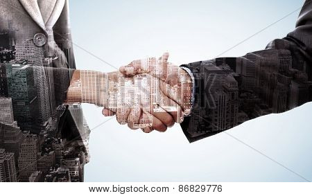 Close up of two businesspeople shaking their hands against high angle view of city