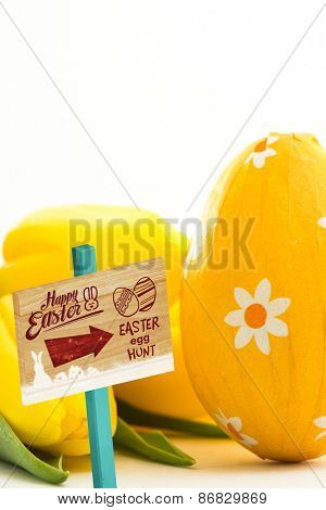 Easter egg hunt sign against yellow easter egg with yellow tulips