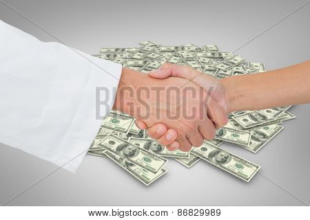 Extreme closeup of a doctor and patient shaking hands against pile of dollars