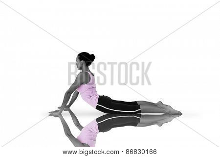 Side view of a fit young woman doing the cobra pose against mirror