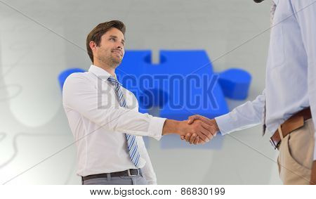 Young businessmen shaking hands in office against jigsaw