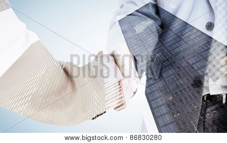 People in suit shaking hands against skyscraper