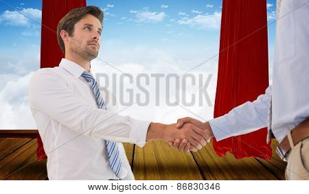 Two businessmen shaking hands in office against stage with red curtains