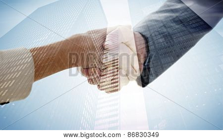 Closeup of shaking hands after business meeting against low angle view of skyscrapers