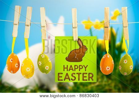 Happy Easter greeting against white fluffy bunny sitting beside daffodils with easter eggs