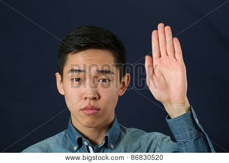 Strict young Asian man giving the stop sign and looking at camera