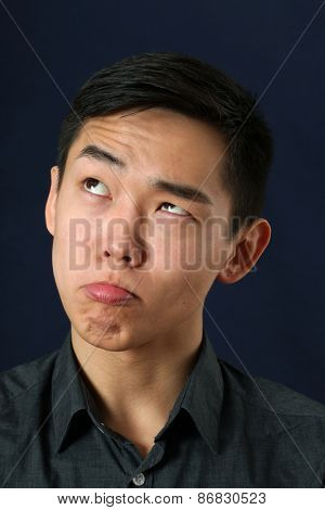 Young Asian man making face and looking upward