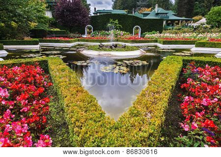 Exquisite fountain among the flower beds. Delightful landscaped and floral park Butchart Gardens on Vancouver Island