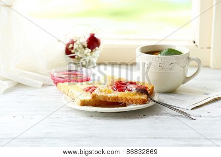 Toasts with jam on plate and cup of tea on light background