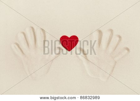 Two hands print in the sand with a red heart. Symbol concept for love, togetherness, friendship or vacation on the beach.