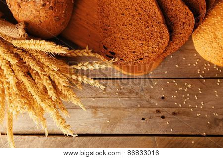 Different bread with ears on wooden background
