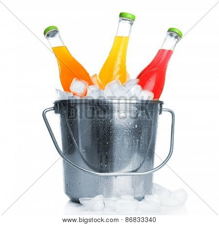 Bottles of tasty drink in metal bucket with ice isolated on white