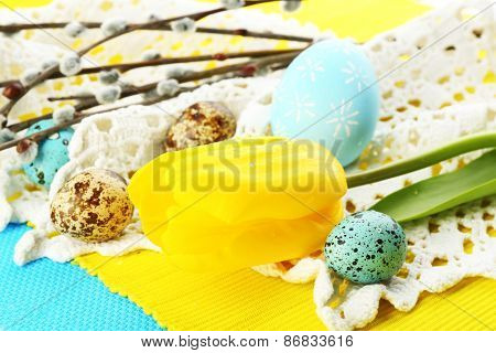 Yellow tulip, colorful eggs and napkins, close-up
