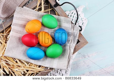 Easter eggs  on wooden tray, on colorful background