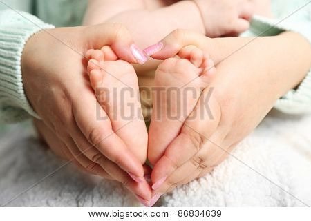 Newborn baby feet on female hands, close-up