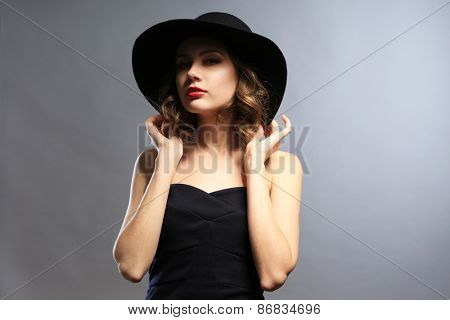 Portrait of beautiful model in black dress and hat on gray background