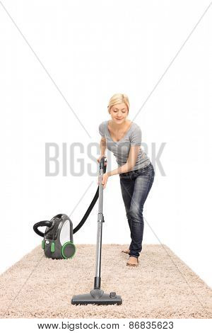 Full length frontal view of a young housewife vacuuming a beige colored carpet isolated on white background