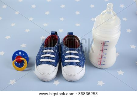 Baby shoes with nipple and bottle of milk on blue background