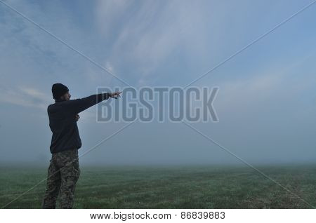 Man involved in sport in the morning. Meadow in the mist.