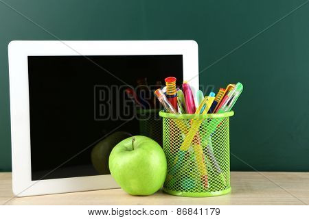 Digital tablet,  colorful pens and apple on desk in front of blackboard