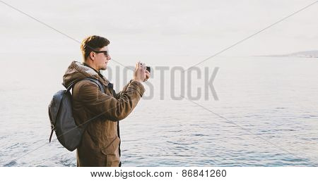 Traveler Taking Photographs On Beach In Spring