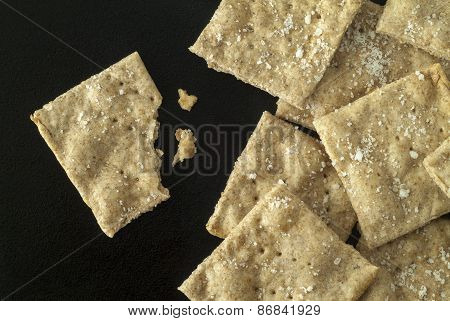 Whole Wheat Crackers With Salt Grains On A Black Iron Surface