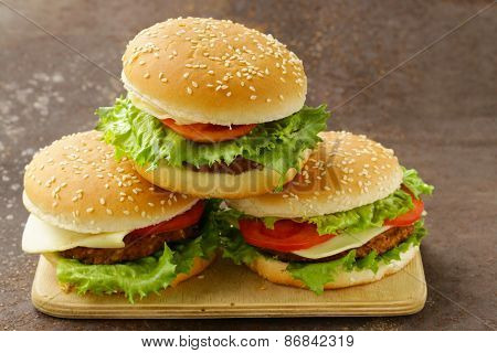 traditional cheeseburger with green lettuce and tomatoes on a wooden background