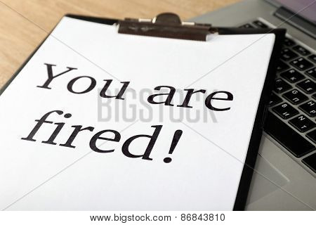 Message You're Fired on laptop keyboard, closeup