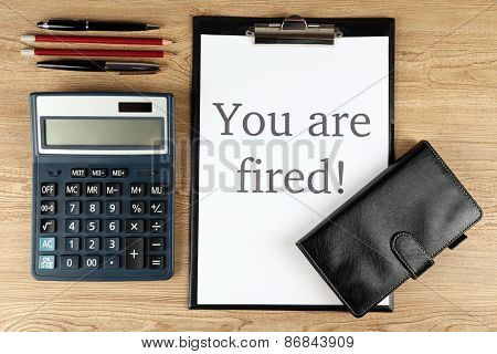 Message You're Fired on clipboard on wooden table, top view