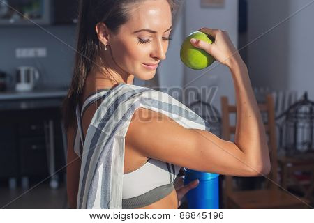 Active athletic sportive woman with towel in sport outfit holding apple showing biceps healthy lifes
