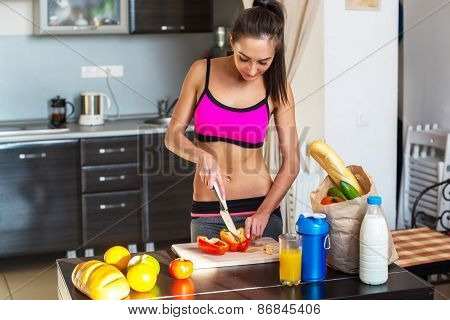 Pretty attractive athletic active sportive lady woman standing in kitchen with a towel on her should