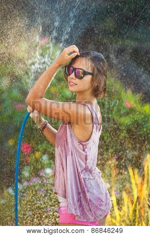 Photo of young woman enjoying shower outdoors