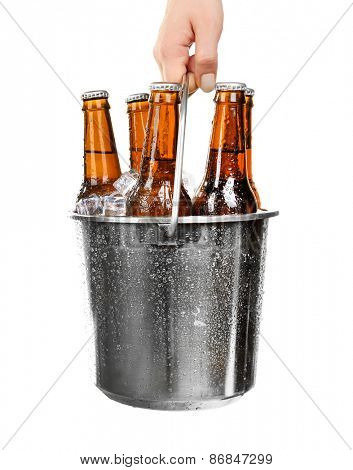 Female hand with metal bucket of beer isolated on white