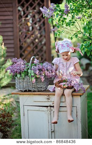 child girl making lilac wreath in spring garden