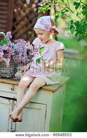 child girl in spring garden cutting lilacs