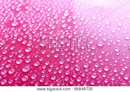 Water drops on glass on pink background