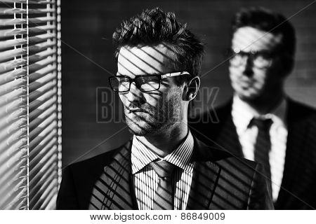 Elegant young businessman in eyeglasses looking through jalousie on background of colleague