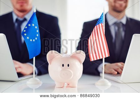 Piggy bank between eu and American flag on background of businessmen typing