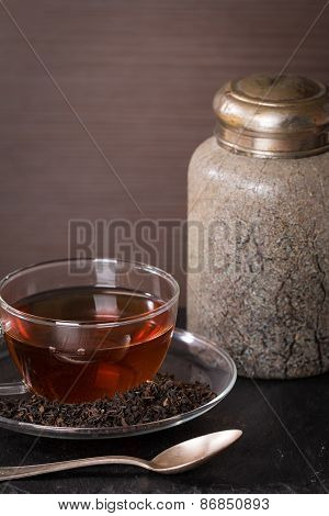 Dry Tea Leaves In Glass Cup Of Tea And Vintage Jar