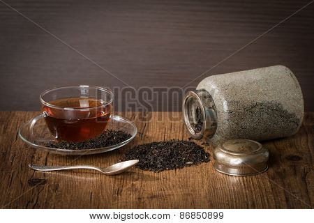 Scattered Dry Tea Leaves With Glass Cup Of Tea