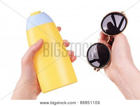 Bottle of suntan cream and sunglasses in female hands isolated on white