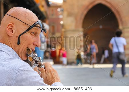 Street Musician Playing The Flute On Piazza Maggiore In Bologna. Italy
