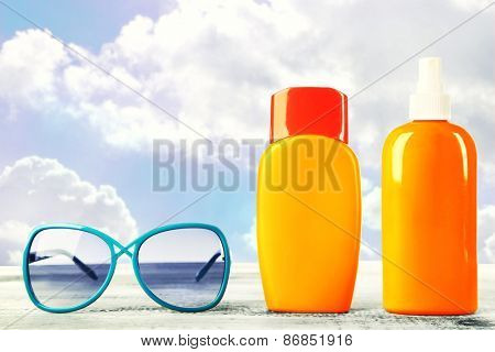 Bottles with suntan cream with sunglasses on table isolated on white