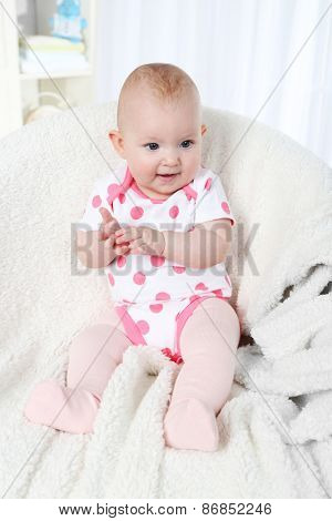 Cute baby girl sitting in arm-chair, on home interior background