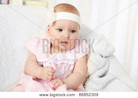 Cute baby girl in pink dress sitting in arm-chair, close-up