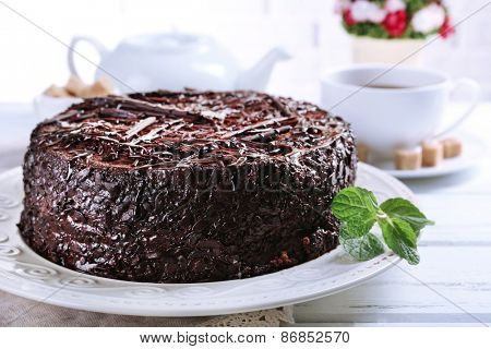 Tasty chocolate cake with mint on table close up