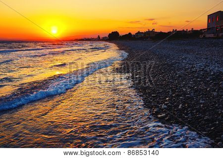 Sunset and sea cobble stone beach