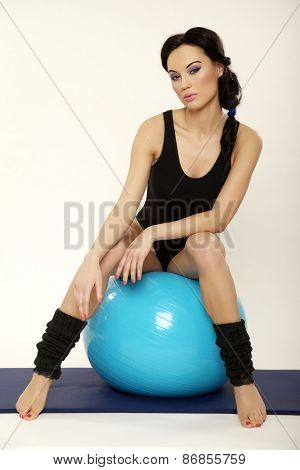 Attractive beautiful young adult pretty brunette sporty woman in black dress with blue fitness ball isolated on white background