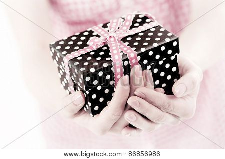 dotted present box in woman hands